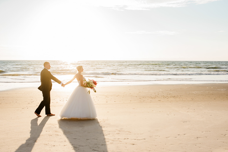Melbourne Beach sunrise wedding groom walking with bride on beach photo by Liz Cowie Photography